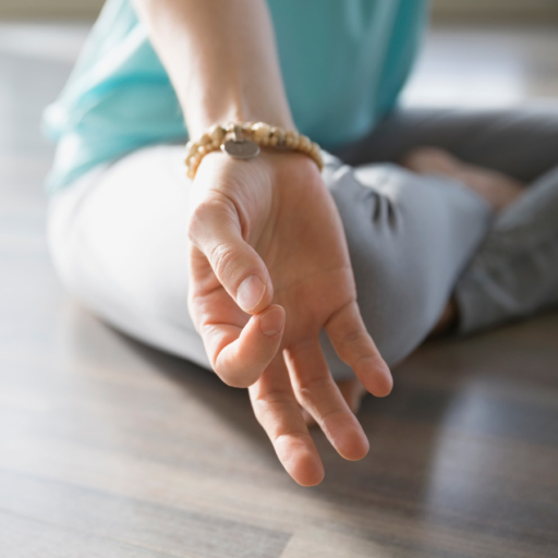 woman sitting on floor meditating