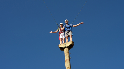 man and woman standing on top of the quantum leap pole at miraval arizona resort & spa