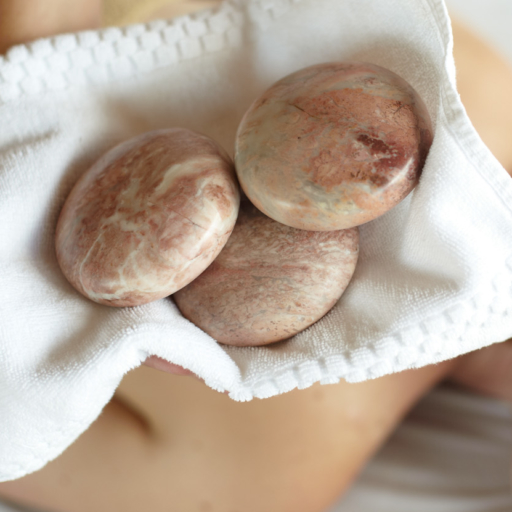 three hot stones in a towel on the upper back of a woman