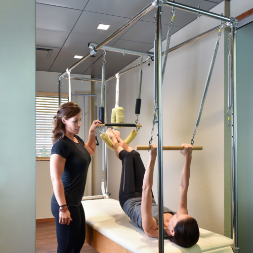 woman and her trainer engaged in pilates apparatus training