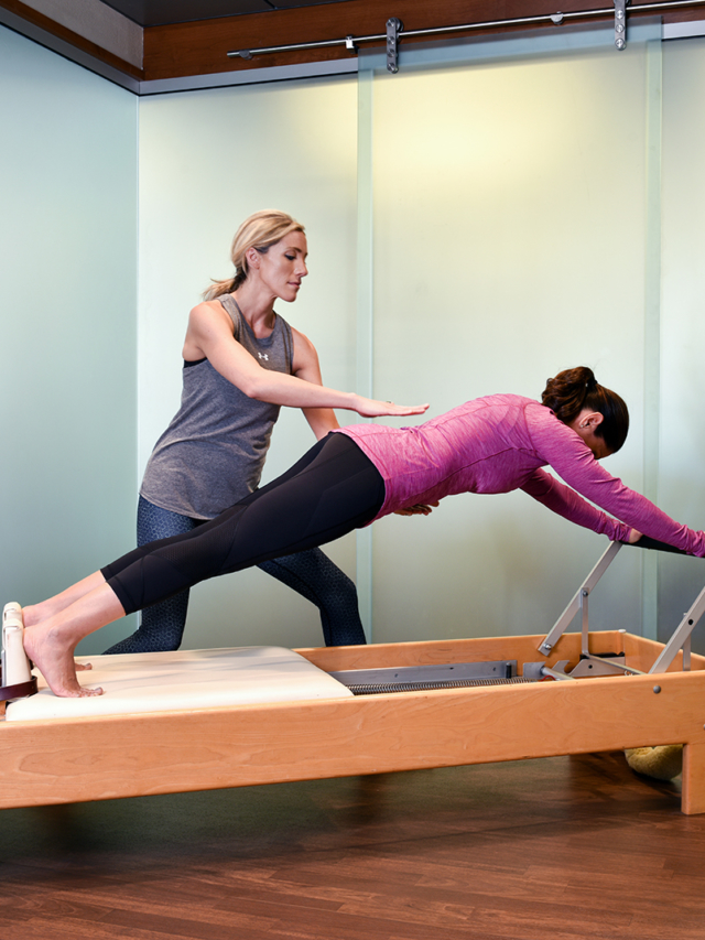 trainer helps a woman stretch in pilates exercise