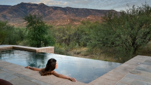 woman relaxing in pool overlooking the tucson desert