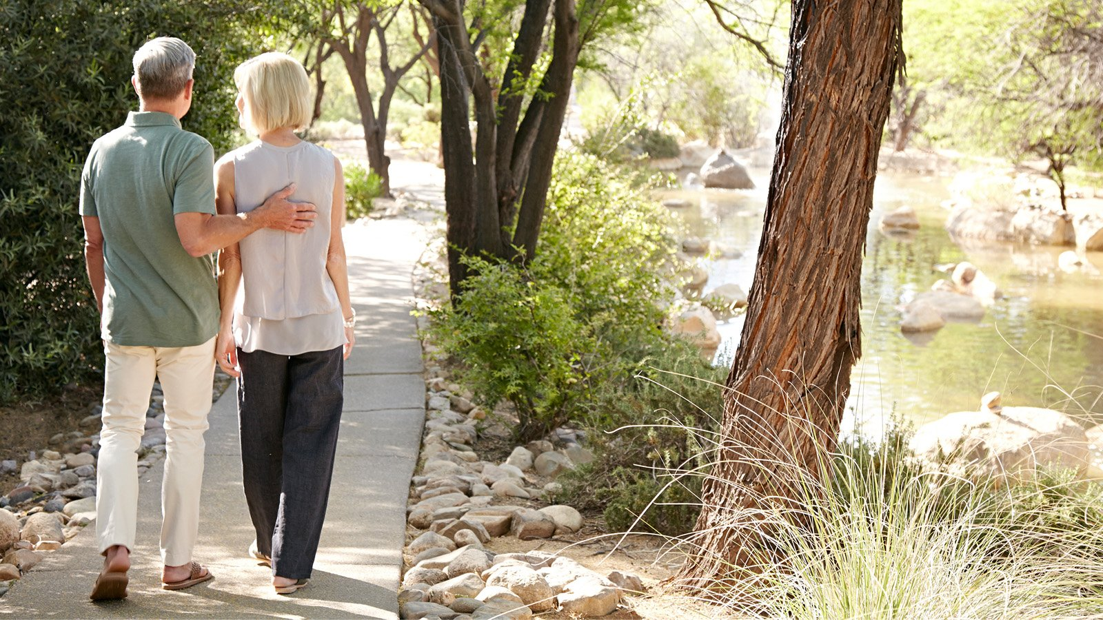 couple taking a walk along a water-side pathway