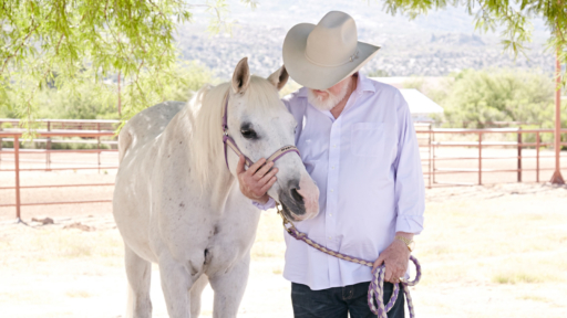 man sharing a gentle moment with a white horse