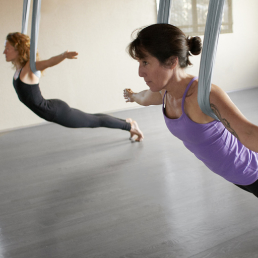 two women using suspended fabrics for aerial yoga