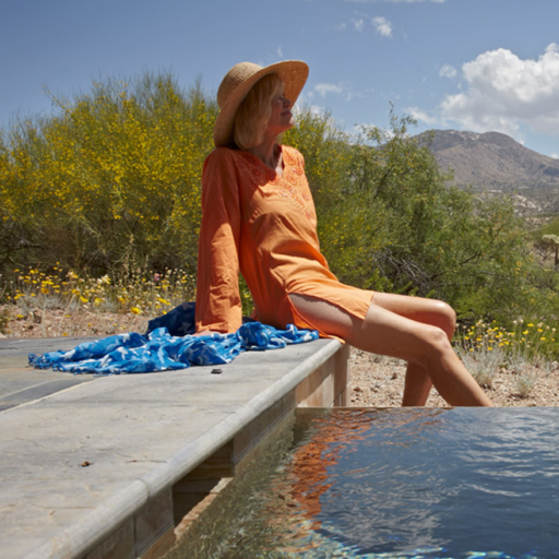 woman sitting on stone bench overlooking the tucson desert