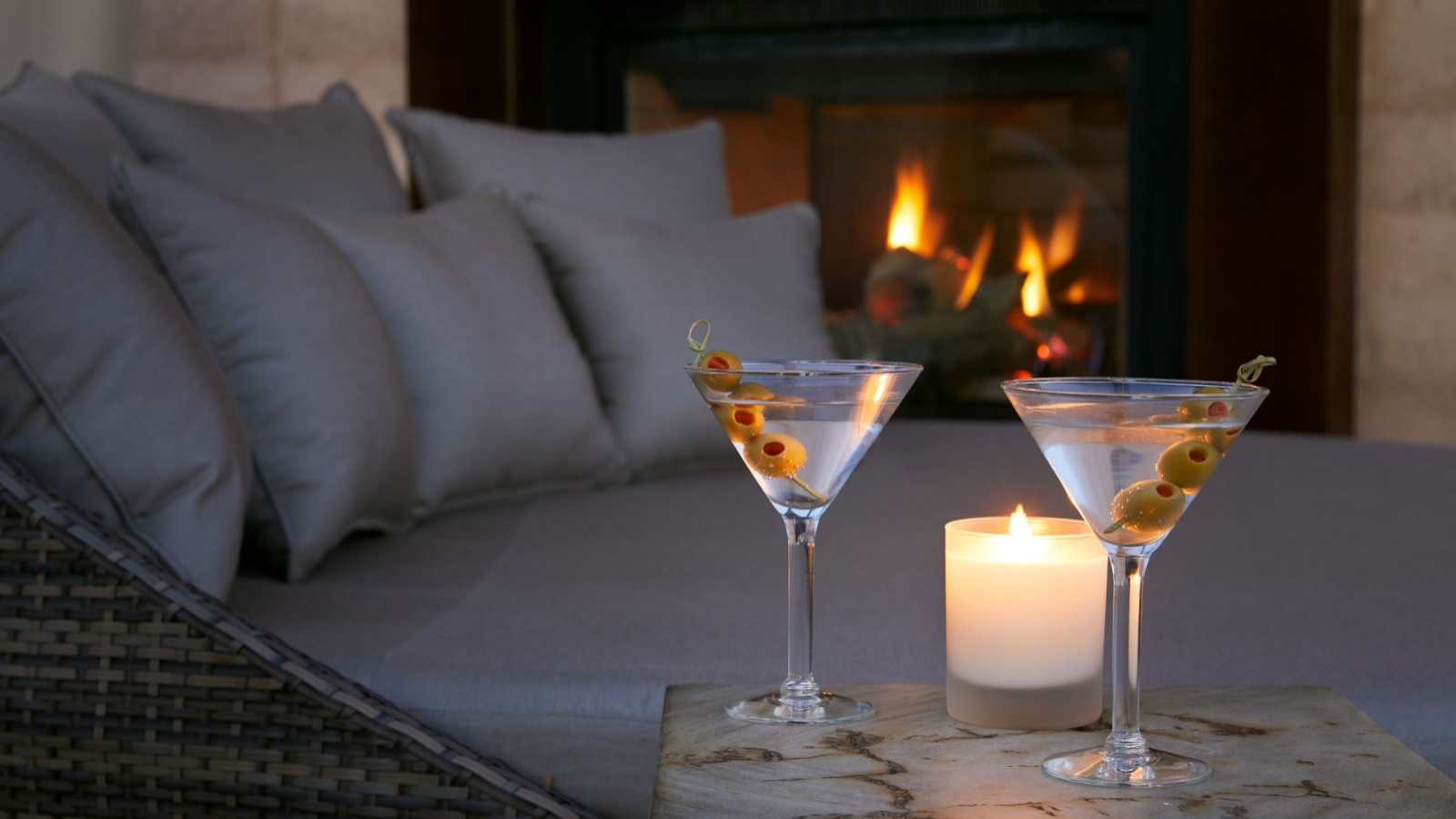 two martini glasses set next to a candle