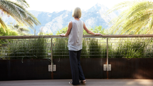 woman looking at scenic view of the mountains through lush vegetation