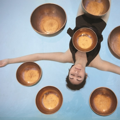 woman floating in a pool of water experiencing a himalayan sound bath