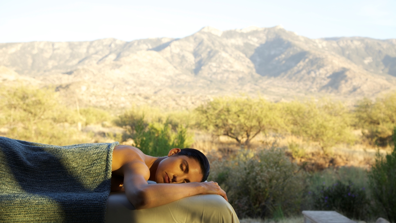 woman laying in massage bed in front of the santa catalina mountains