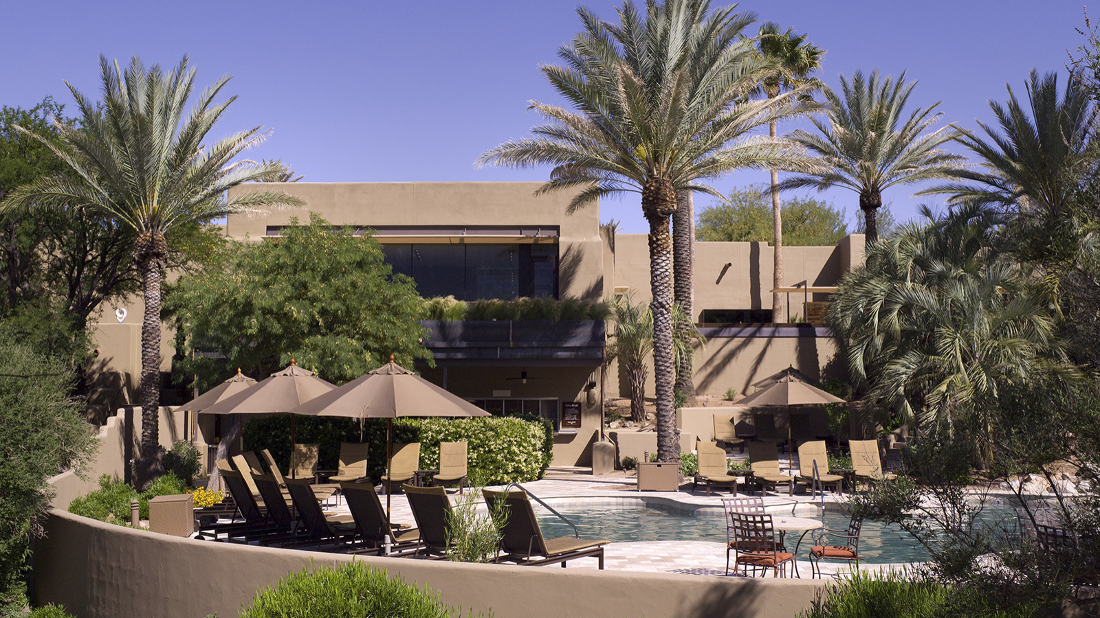 chairs and umbrellas around the pool at miraval arizona resort & spa