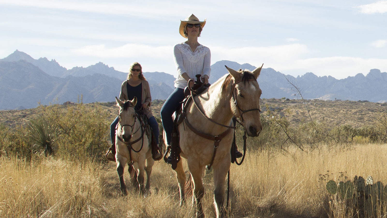 pair of riders on horseback enjoying the desert and mountains