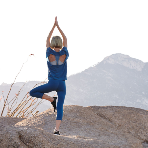 woman standing in a yoga pose on a rock