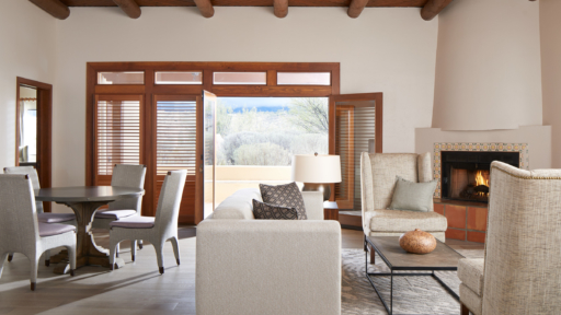 View of villa living room at Miraval Arizona, with fireplace and open door to patio.