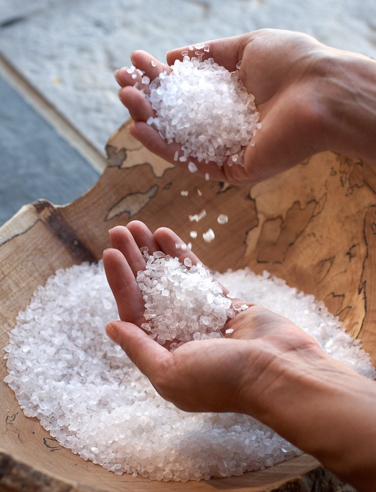 hands holding blend of sea-salt and other botanicals