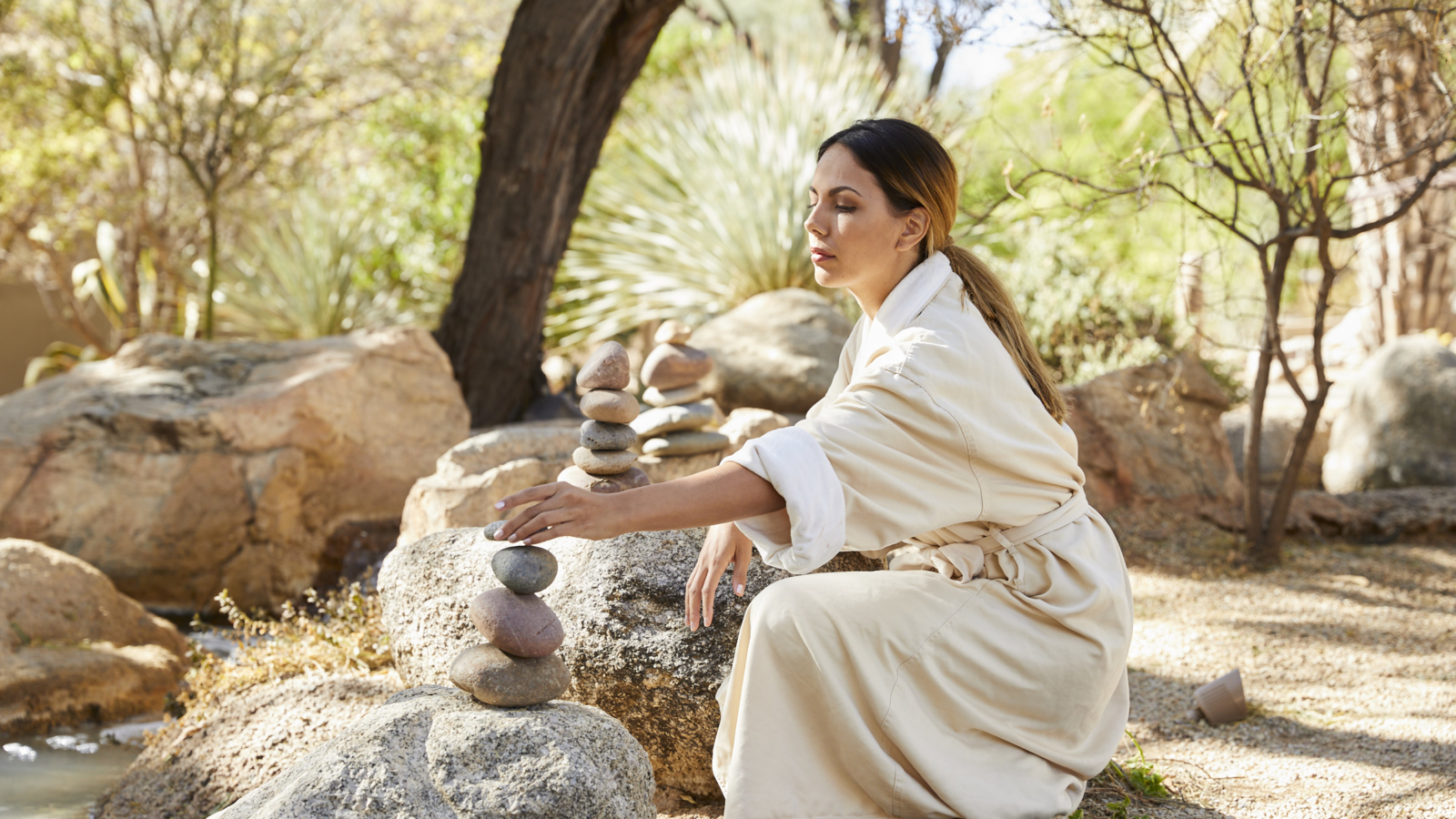 woman building stone cairn in tucson arizona