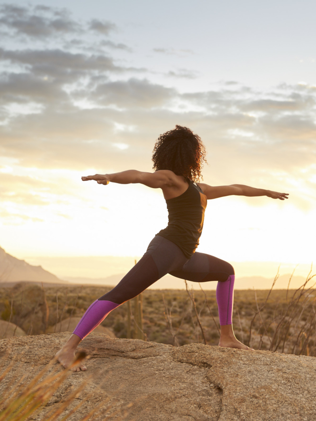 woman performing yoga outdoors in the desert during sunset