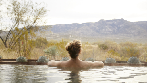 woman in a pool looking at mountain view