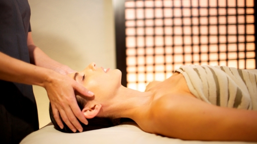 woman lying on massage table receiving scalp massage