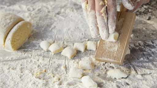 gnocchi dough being rolled against wooden board