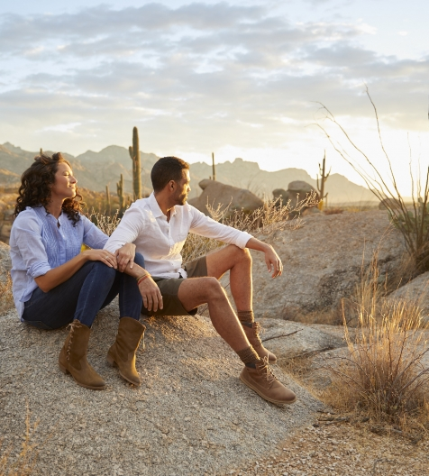 couple sitting on a rock watching the sunset