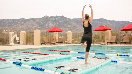 woman balancing on boga fit mat at swimming pool