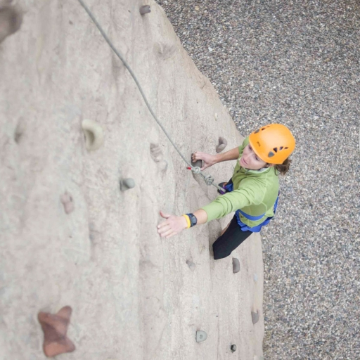 woman scaling the climbing wall