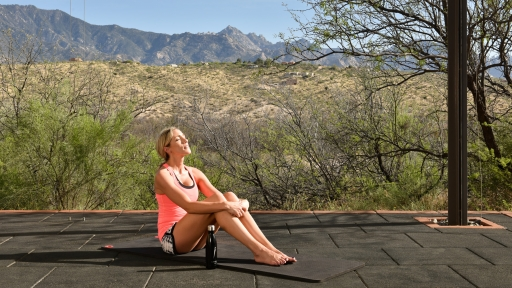 woman sitting on a yoga mat absorbing the sun rays