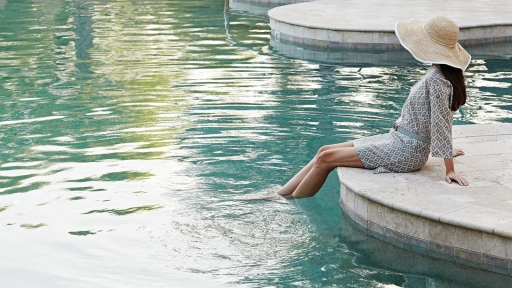 woman sitting on the edge of the pool with her feet in the water