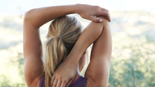 female stretching her arms while gazing outdoors