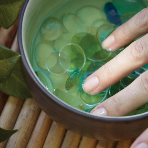 Closeup of woman putting fingers in water bowl with shells at Miraval Arizona.