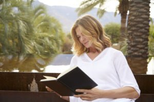 Close up of blonde woman reading book outdoors at Miraval Arizona.