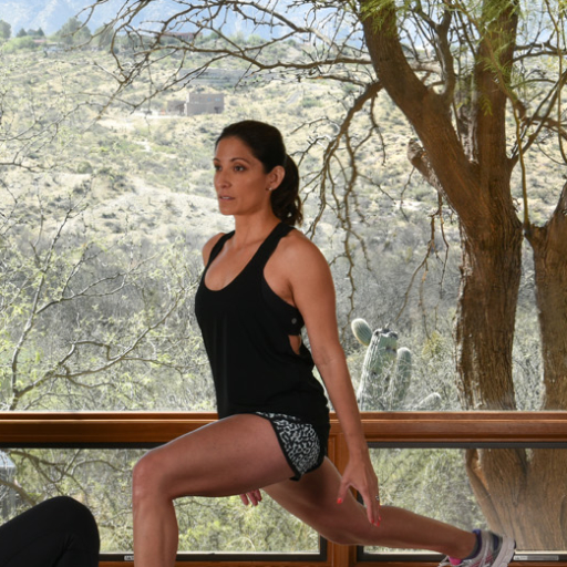 Woman performs standing lunge during fitness class at Miraval Arizona.