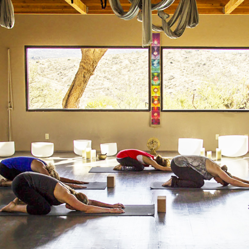 Group of women perform yoga child pose at Miraval Arizona.