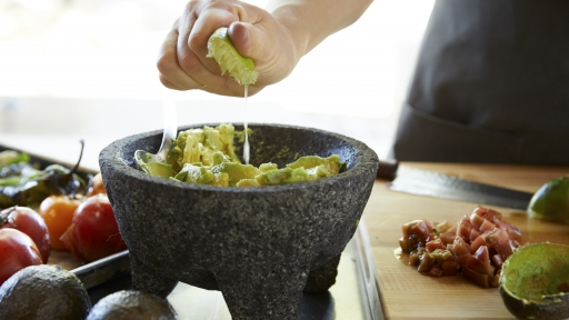 Close up of cook squeezing lime into avocado bowl at Miraval Arizona.