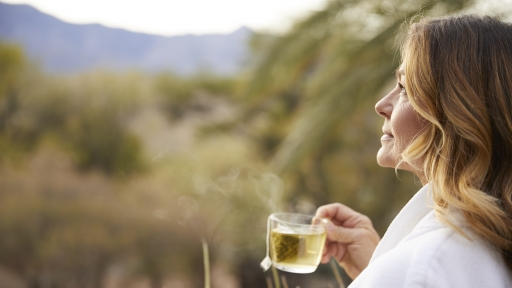 Woman enjoys a cup of tea while soaking in the outdoors at Miraval Arizona.