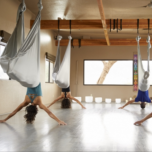 group practicing aerial yoga