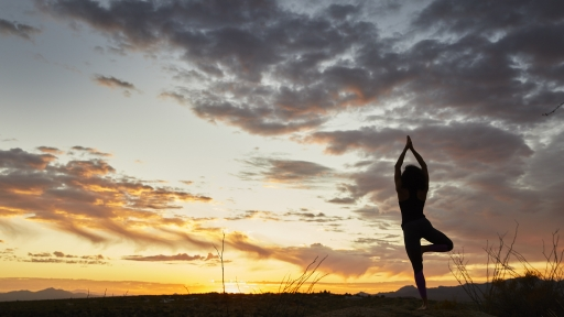 Woman performs standing yoga pose during sunset outside Miraval Arizona.