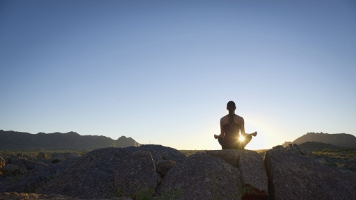 woman meditating on top of a rock in the tuscon desert