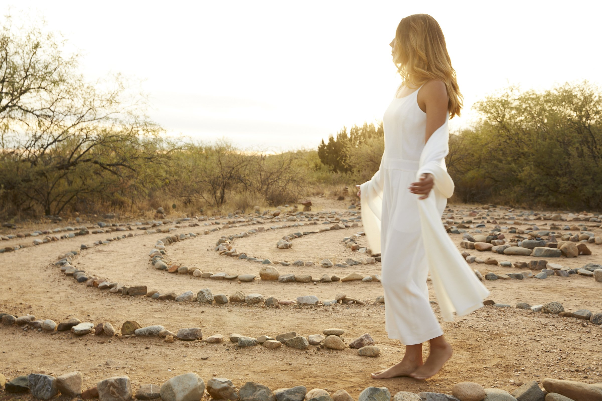 woman reflecting in the labyrinth journey at sunset
