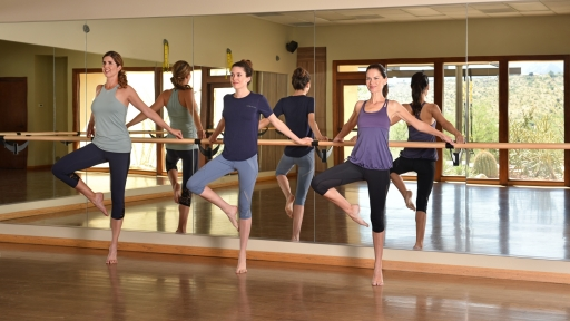 Trio of women perform stretch pose in fitness center at Miraval Arizona.