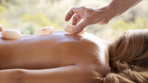 smooth stones being placed during spa treatment