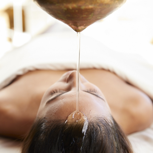 warmed oil for abhyanga massage being poured