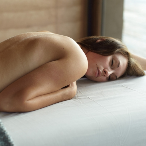 woman laying on white massage bed at miraval arizona resort & spa