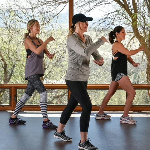 three women doing a mindful energy movement exercise indoors