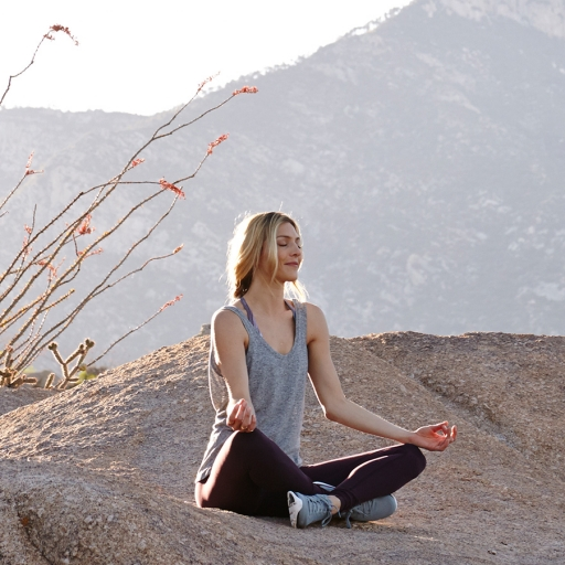 woman meditating on a mountain rock