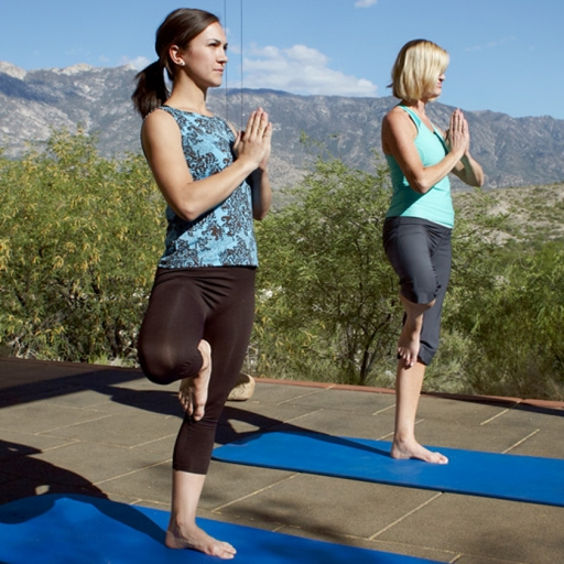 women practicing yoga in front of the santa catalina mountains