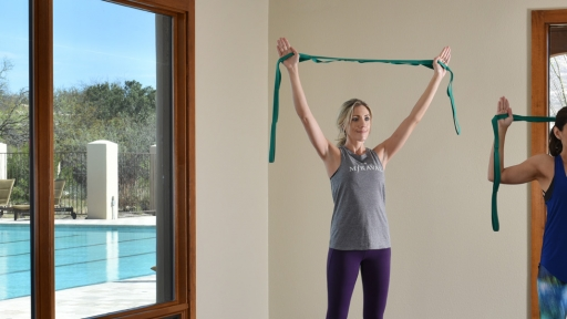 two women stretching there arms using resistance bands