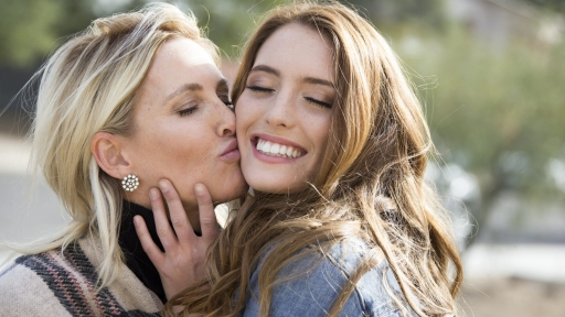 woman kissing another woman on the cheek