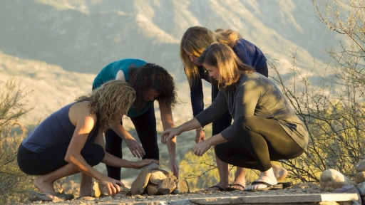 group of women gathered together stacking stones